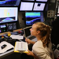 Artist-At-Sea participant Lauren Salm monitors incoming data from R/V Falkor's mulitbeam sonar.